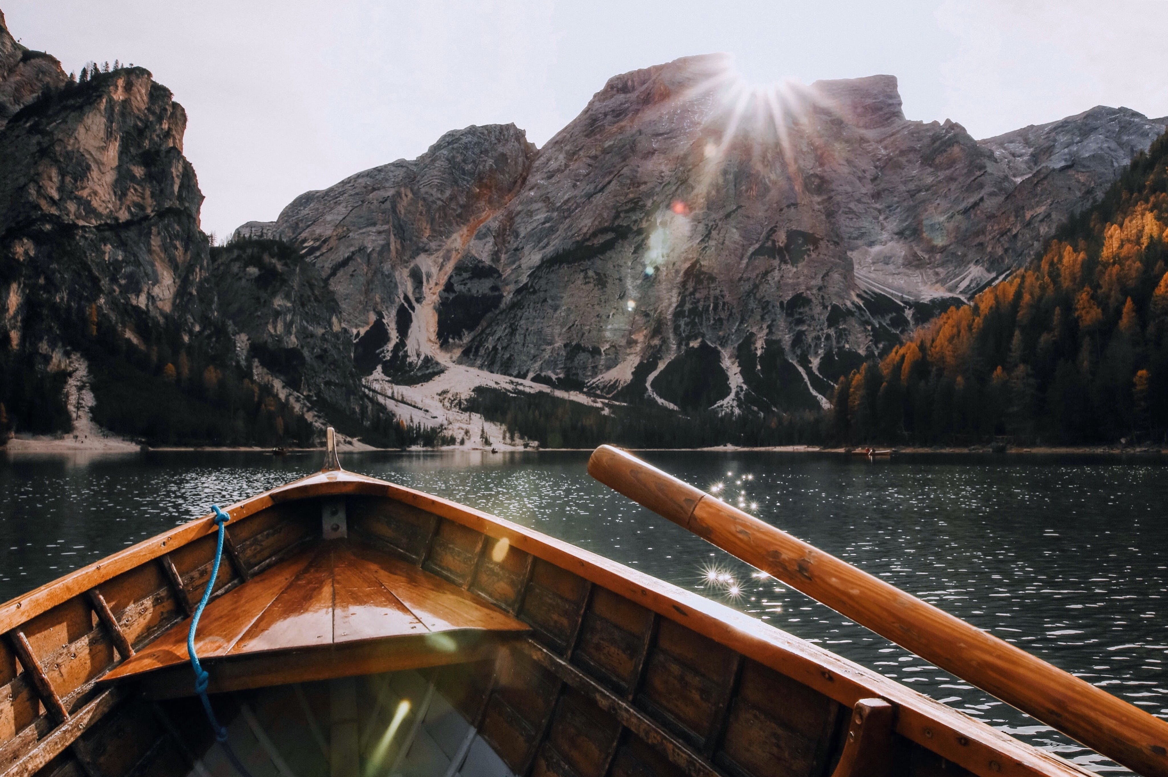 Brown Canoe in the Body of Water Near Mountain