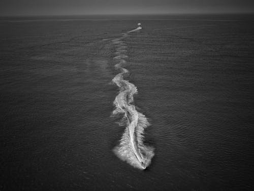 Black and white drone view of fast motorboat sailing in deep dark endless sea and forming waves and splashes in daylight