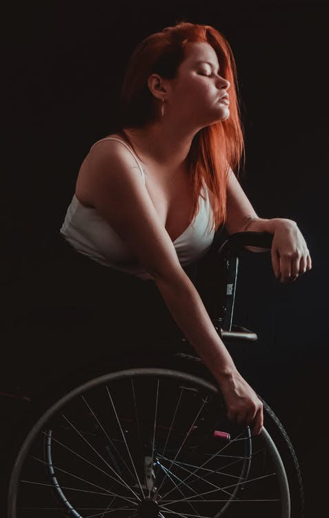 Woman in White Tank Top Sitting on Black and Silver Wheel Chair