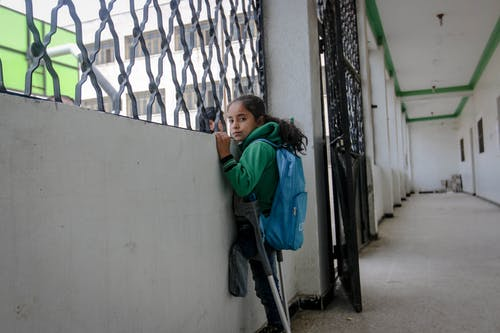 Poor ethnic injured girl with crutches and backpack