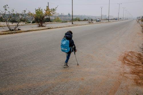 Girl with leg amputation on asphalt road in gloomy weather