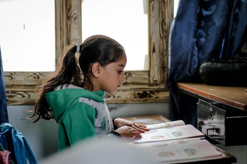 Side view of smart ethnic girl with dark hair learning with book in old school