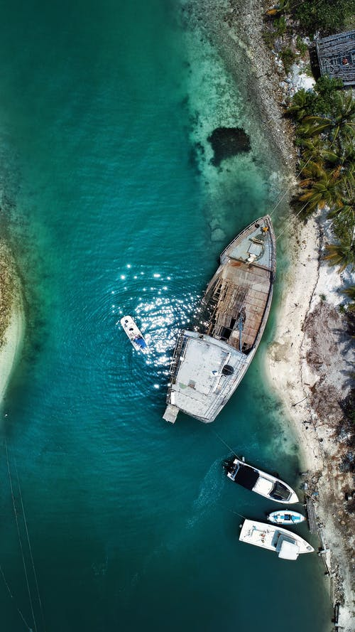 Top view of nautical transport near rough uneven coast of rippling azure bay