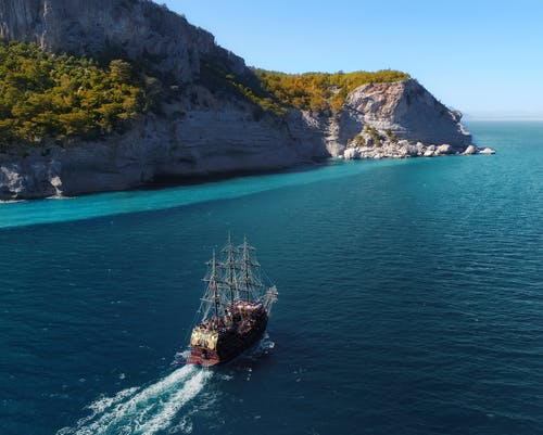 Drone view of aged sail ship floating in rippling blue ocean near rocky mountainous island with green trees and plants under blue cloudless sky in sunny summer day