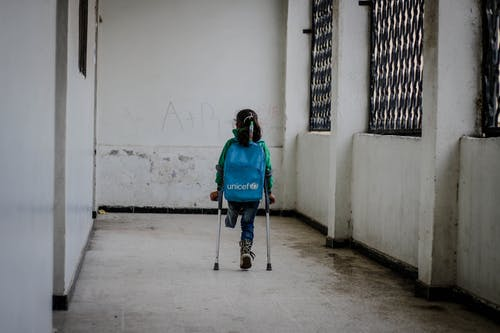 Girl with leg amputation walking in corridor