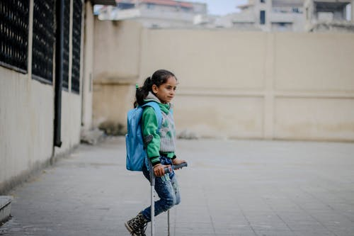 Side view of ethnic girl with backpack looking away on shabby street in daytime