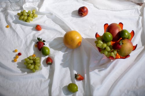 Ripe tasty fruits in glass vase and on white textile