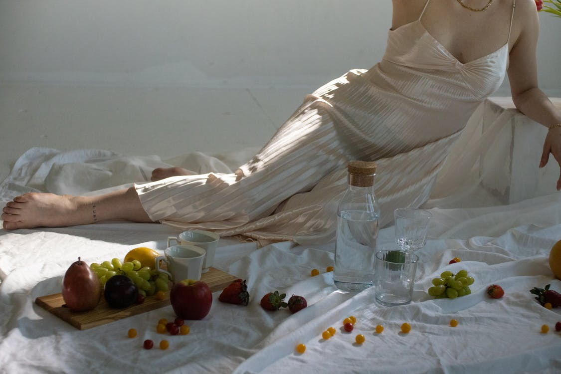 Woman resting near glassware and sweet fruits on wooden board
