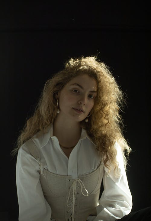Young female with long curly hair in white shirt and corset looking at camera on black background