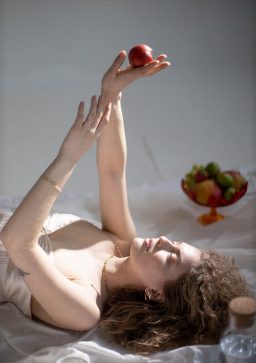 Young female with long curly hair bare shoulders and chest and closed eyes lying on bed and holding fresh red apple