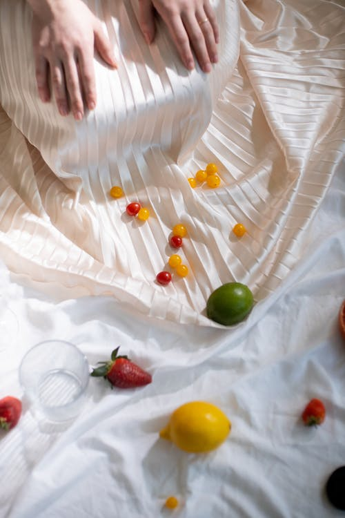 Green and Red Fruits on White Textile