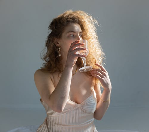 Young female with curly hair bare shoulders and chest looking away while drinking water on white background