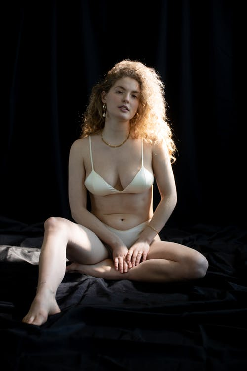 Woman in White Brassiere Sitting on Black Textile