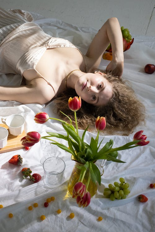 High angle of sensual woman with curly hair in silk dress relaxing on floor near to vase with flowers and coffee cups and scattered fruits