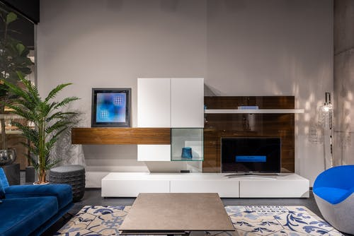 Creative interior of spacious living room with comfortable sofa and armchair and modern TV set placed on minimalist styled cabinet in daylight