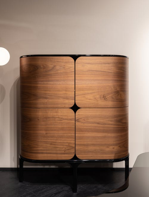 Minimalist wooden cabinet with rounded edges in room