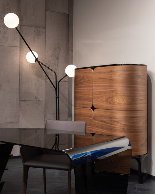 Empty table with chair placed near wooden cabinet at wall with creative glowing lamps inn modern workspace of stylish office