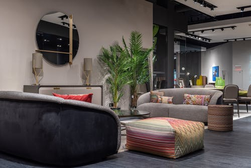 Interior of modern apartment with soft couches and colorful cushions and poufs placed near wall with mirror and decorations in modern apartment with green plants