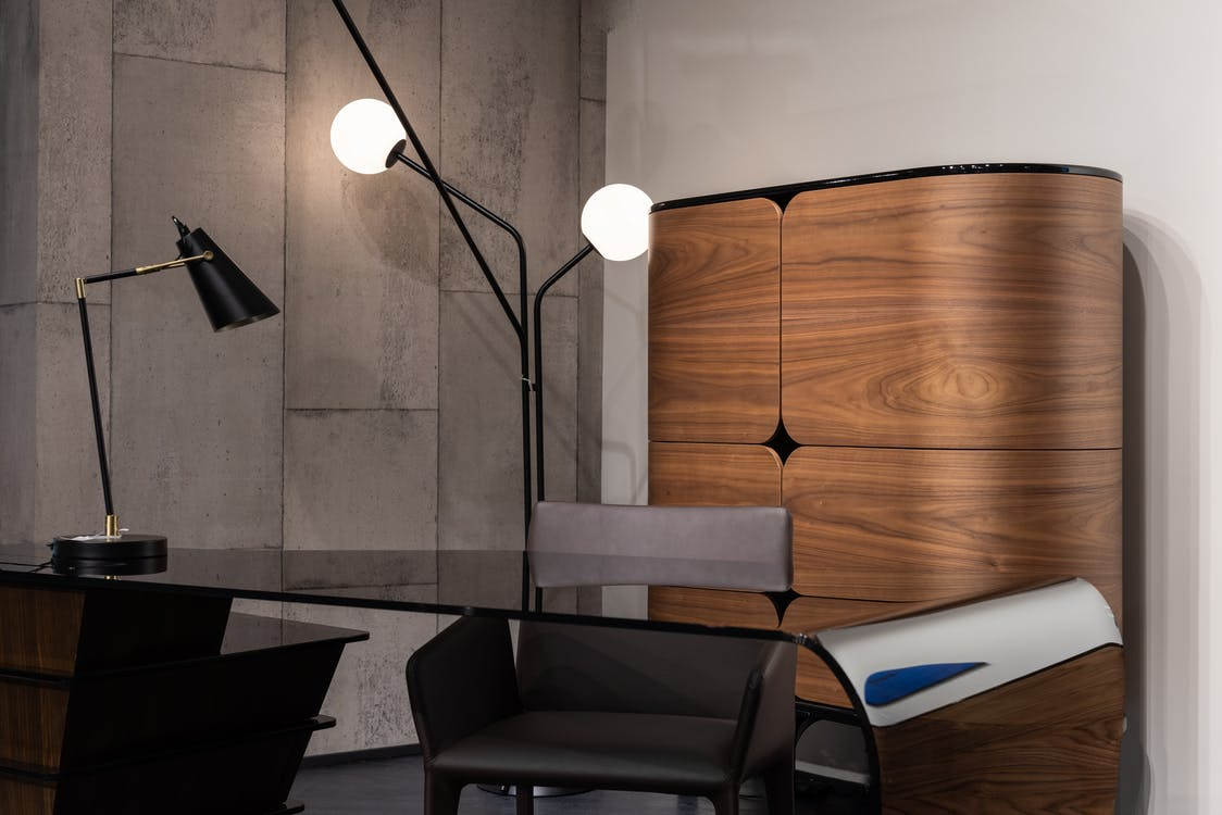 Black desktop with comfortable chair placed at wall with wooden cupboard and glowing lamps in modern workspace in creative office