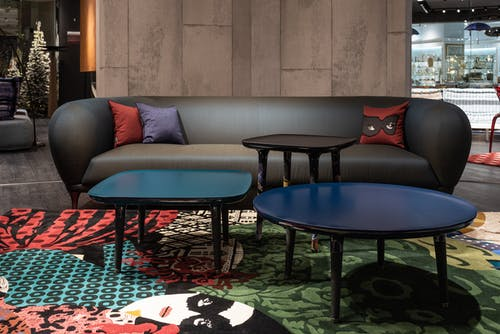 Stylish couch on rug near tables