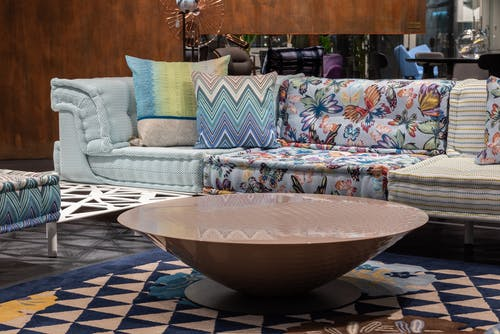 Comfortable sofa with colorful cushions placed near modern table on rug in contemporary living room of spacious apartment with pouf