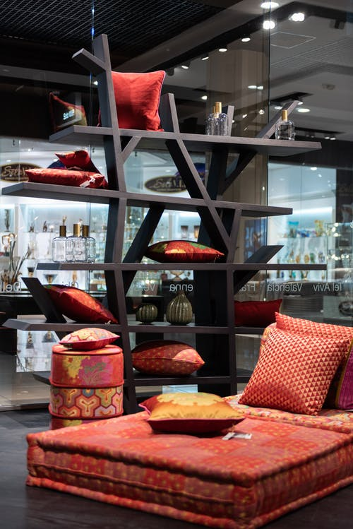 Comfortable colorful poufs with bright red pillows on black shelves with decorations placed in modern shopping center with glass showcases