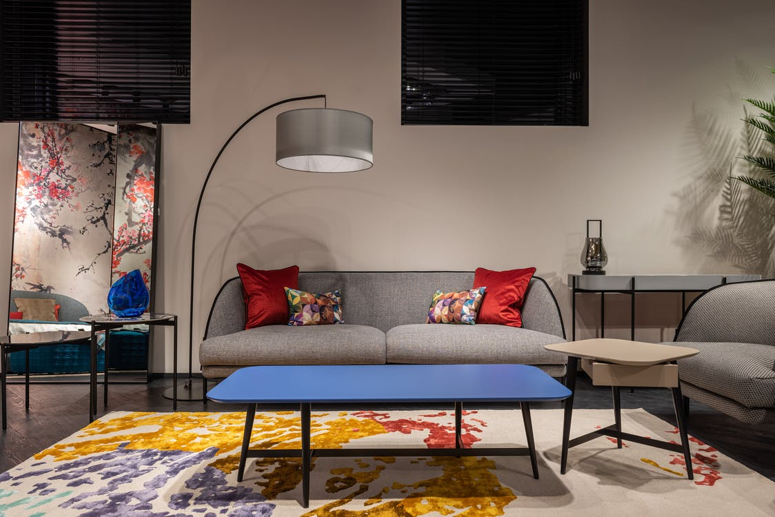 Comfortable sofa with colorful cushions placed at wall near armchair and table on carpet in spacious living room with lamp
