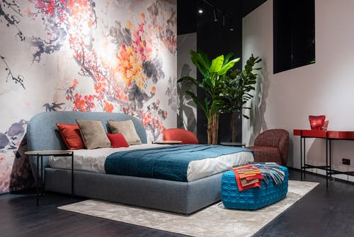 Comfortable bed with colorful cushions and blue blanket placed at painted wall in modern bedroom with armchairs and potted plant