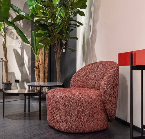 Soft red armchair placed near small round side tables at wall with green deciduous plants in modern room with stylish interior