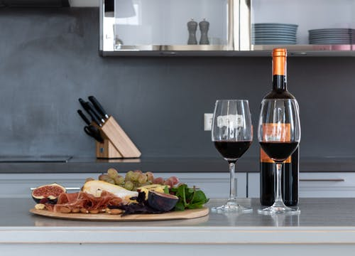 Goblets with red wine placed on counter with bottle of alcohol drink and tray with assorted fruits and meat in kitchen