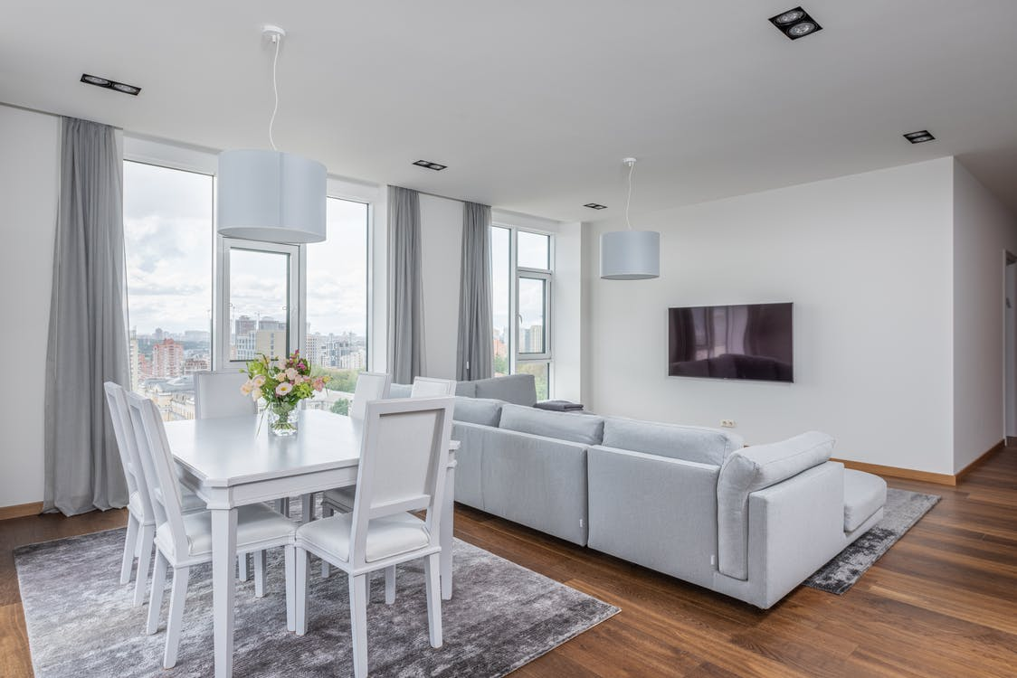 Vase with flowers on white table near chairs placed on rug near couch against wall with TV in stylish apartment with big windows