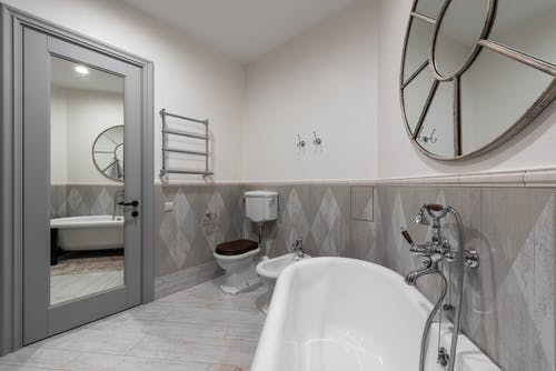 White bathtub with faucet at tiled wall placed near toilet and bidet in contemporary bathroom with mirror with reflection on door