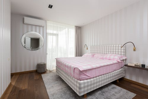 Interior of bedroom with comfortable bed and light walls