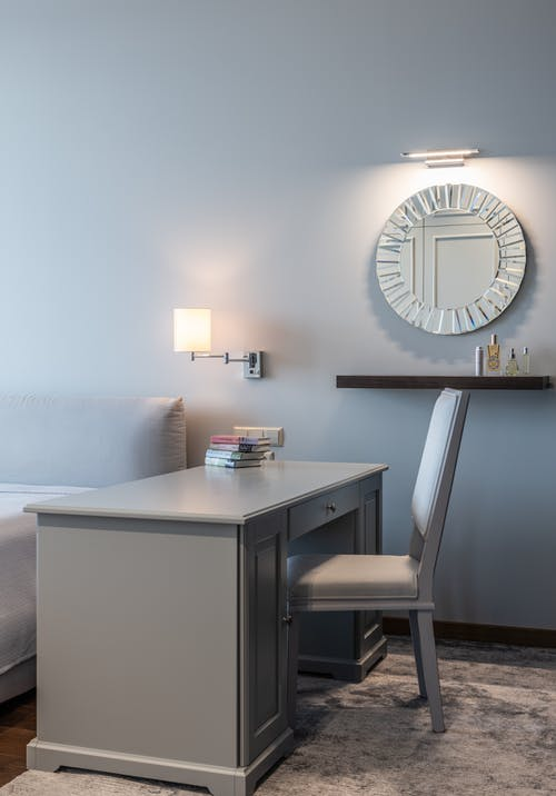 Table with stack of books placed against wall with round mirror in light modern room in apartment