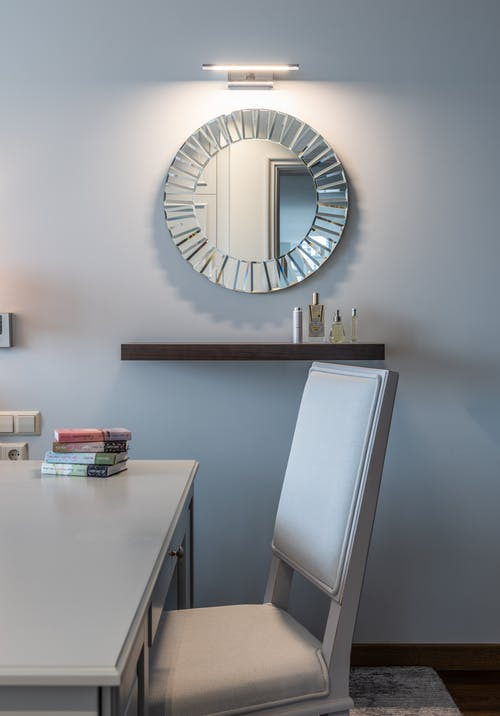 Table and comfortable chair against wall with round mirror in apartment