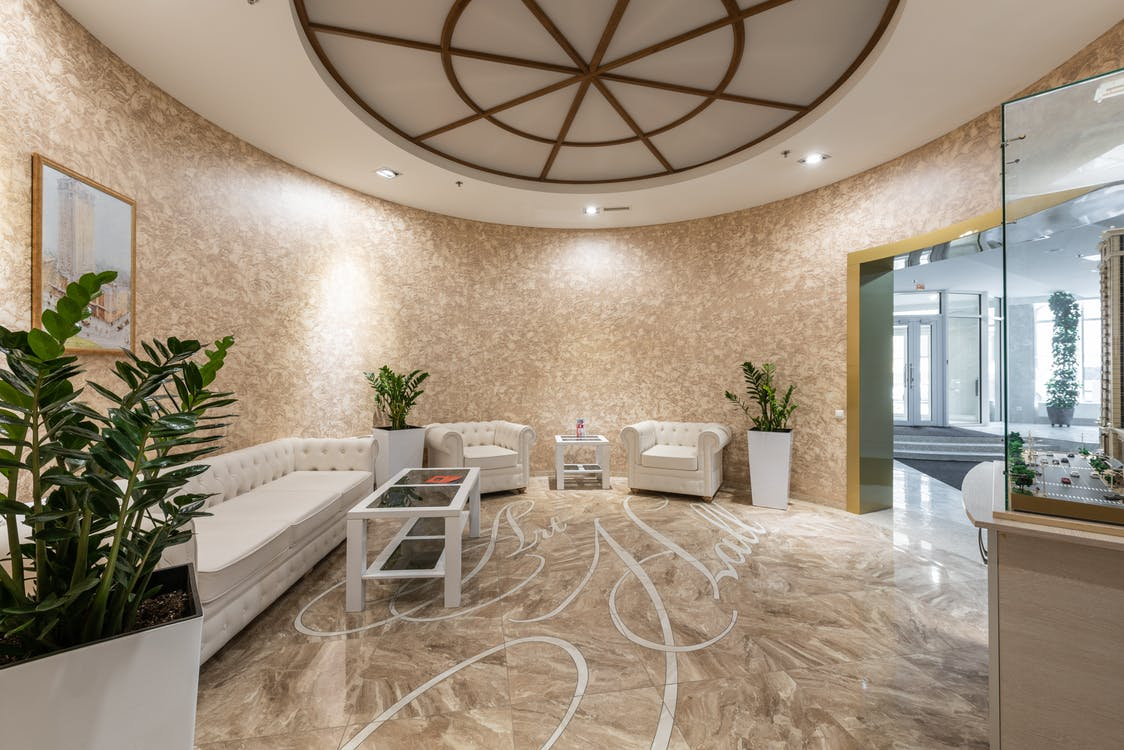 Interior of spacious lobby with comfortable white sofa and armchairs placed in contemporary hotel in daylight