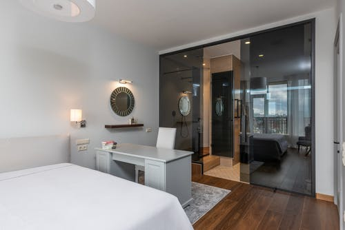Contemporary interior of bedroom with furniture in minimalistic style and glass walls placed in modern apartment in daylight