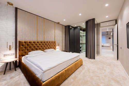 Interior of light spacious apartment with bed and table near wardrobe with curtains and door to living room