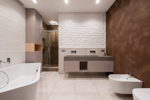 Interior of modern light bathroom with bidet and toilet in front of bath and cabinet with sink and faucet next to shower