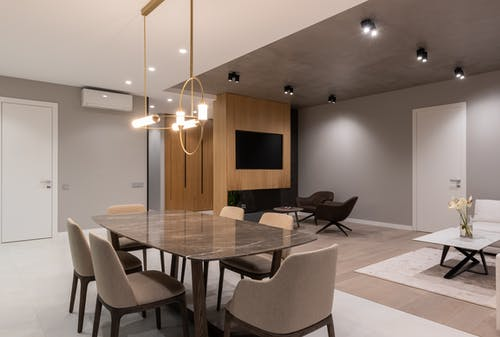 Interior of modern bright home with dining table with chairs under lamps hanging on ceiling next to armchairs with TV on wall and doors