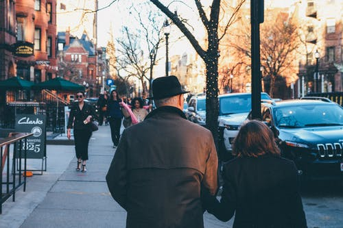 Man in Black Hat Holding His Wife