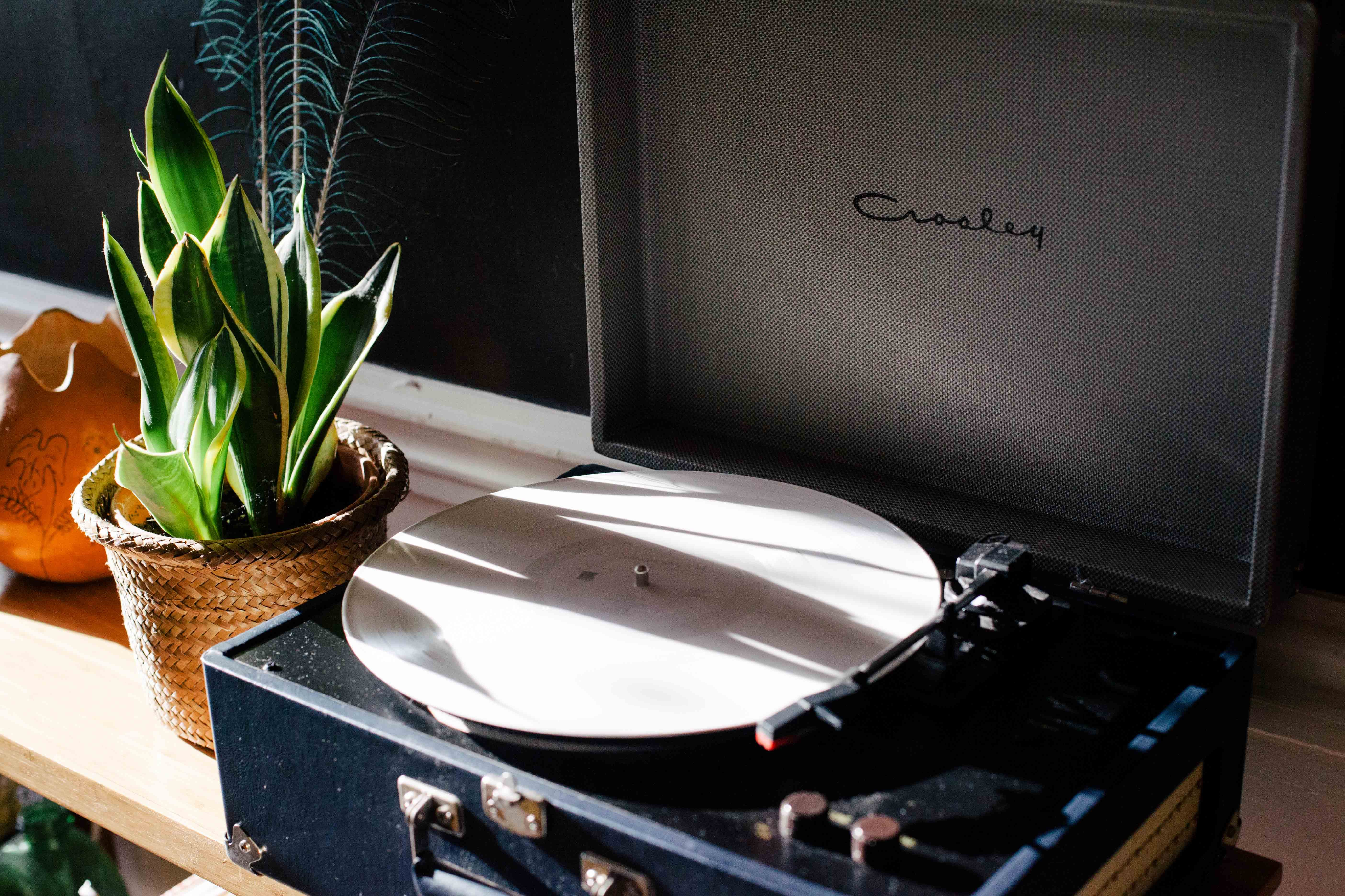 Black and White Crosley Vinyl Record Player on White Wooden Frame