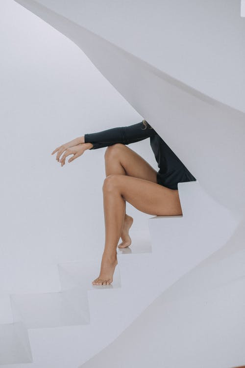Woman in Black Mini Skirt and White Shoes Sitting on White Wall