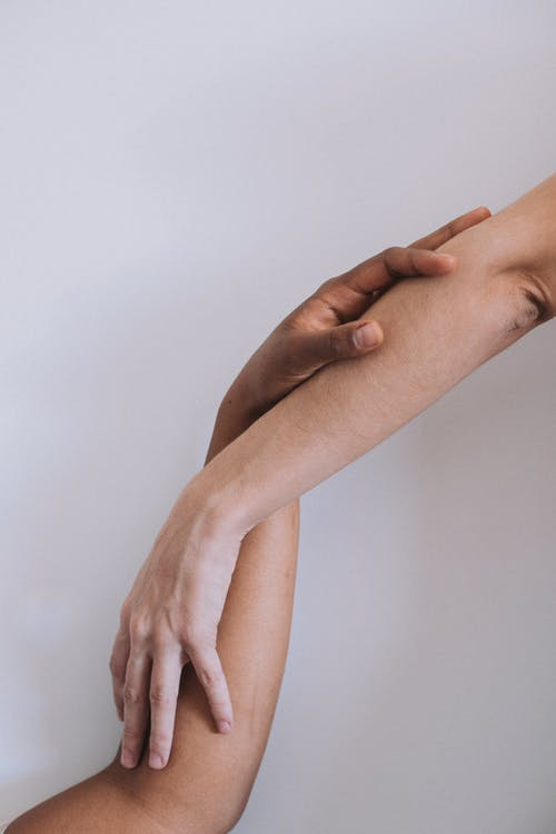 Crop hands of anonymous multiethnic couple touching hands in light studio