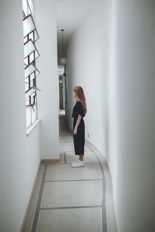Woman in Black Shirt and Black Pants Standing on Staircase