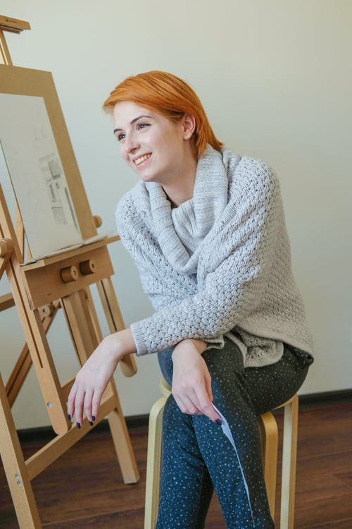 Happy young woman sitting near easel in workshop and smiling
