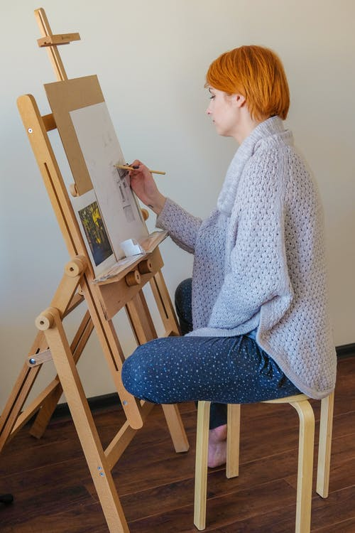 Concentrated female painter working in art studio