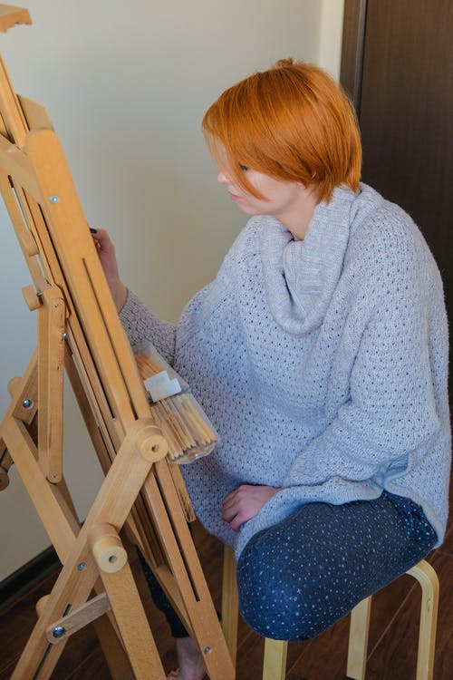Talented young woman painting on easel in room