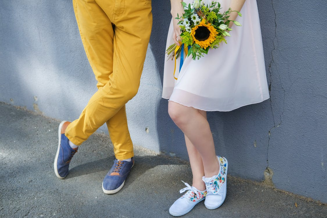 Young romantic couple with sunflower bouquet standing on street