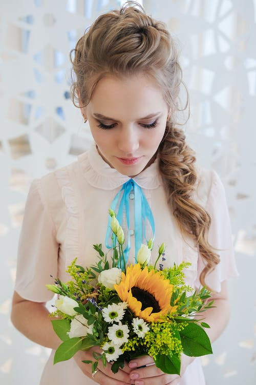 Feminine young woman with bouquet of fresh flowers standing in light room